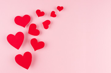 Red paper hearts soar on pink color background, copy space. Valentines day backdrop.