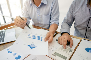 two businessman working together with financial report