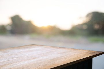 empty wooden desk over blurred montage home garden with sunset background