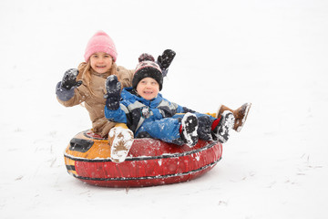 Image of cheerful girl and boy riding tubing