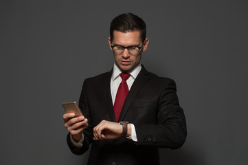Successful young man hurrying on meeting and looking at his watch with smartphone in his hand on gray background.