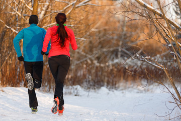 Photo from back of sports woman and man running on winter