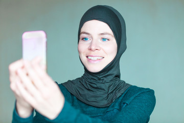 woman in hijab takes pictures with herself smartphone
