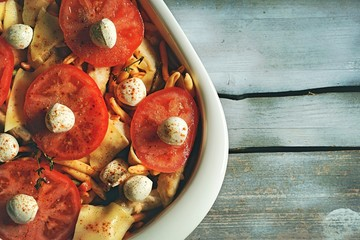 casserole. the dish is decorated with pieces of tomato and mozzarella cheese