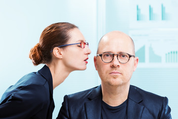 Woman whispering into man ear at office