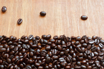 Roasted coffee beans on red-grey wooden background
