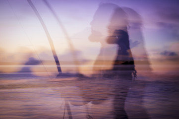Abstract, multiple-exposure, motion blur image of tropical sunset an berimnau player
