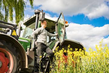 Agrarwende - Junglandwirt auf seinem Traktor mit Blick auf eine unsichere Zukunft