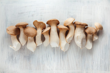 set of edible mushrooms on white wooden kitchen plate can be used as background