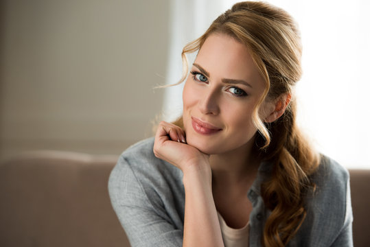 portrait of beautiful young woman sitting with hand on chin and smiling at camera