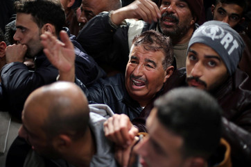 Man gestures as he asks for a travel permit to cross into Egypt through the Rafah border crossing after it was opened by Egyptian authorities for humanitarian cases, in the southern Gaza Strip