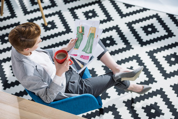 high angle view of young fashion designer with cup of coffee looking at sketches