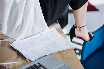 cropped shot of fashion designer sitting on work table with sketches