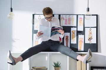 fashion designer sitting on bookshelves and reading magazine