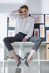 beautiful stylish fashion designer sitting on bookshelves