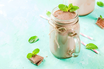 Fotobehang Milkshake Chocolate smoothie or milkshake with mint and straw, in mason jar on light blue background, copy space