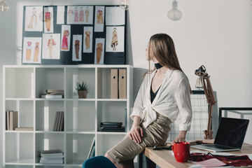 stylish fashion designer sitting on table at office and looking at sketches