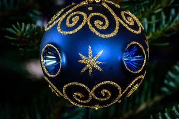 Macro shot of a blue ball shaped ornament on a Christmas tree