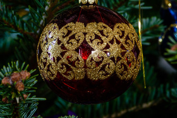 Macro shot of a red ball shaped ornament on a Christmas tree