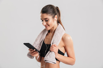 Portrait of young woman in gym posing with towel on neck and listening to music using earphones and smartphone, isolated over gray background