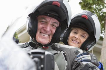 Portrait of smiling senior couple wearing helmets on motorcycle