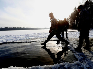 A soldier of NATO's Enhanced Forward Presence battle group jumps in the icy water during the winter survival exercise in Adazi