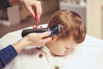 Little boy at the hairdresser. Child is scared of haircuts. Hairdresser's hands making hairstyle to little boy, close up