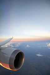 Aircraft turbo prop jet engine and wingtip in flight with sunset sky