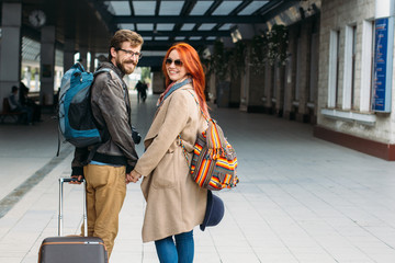 Rear view of amorous hipster couple walking down station and chatting outdoors. Holyday and weekend concept