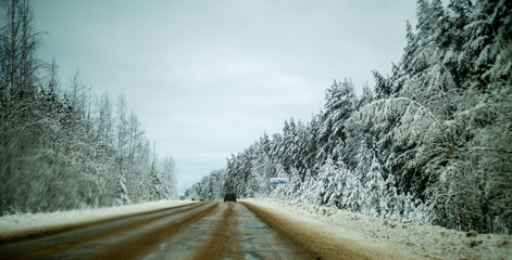 Photo of winter road with trees in snow
