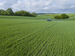 Tractor spraying crop in green farm fields with pesticide