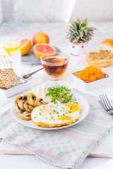 Healthy breakfast plate with scrambled eggs, cheese, grilled mushrooms and sprout micro greens and other snacks and drinks on the served white wooden table. Selective focus.