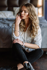 A girl with long blond hair dressed in black jeans, a striped shirt and black shoes sitting on the bed with blue linens. Fashionable casual outfit.