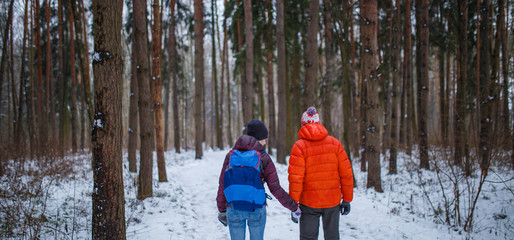 Photo of man and woman on walk in winter forest