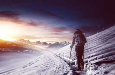 Hiker walking along snowy path in mountains