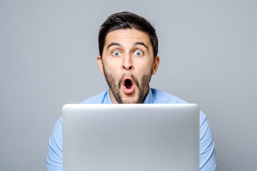 Portrait of amazed man with laptop computer