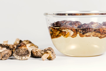 Shiitake mushroom between dry and wet on the white background.