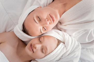 Absolute relaxation. Nice peaceful beautiful mother and daughter lying together and closing their eyes while enjoying their relaxation