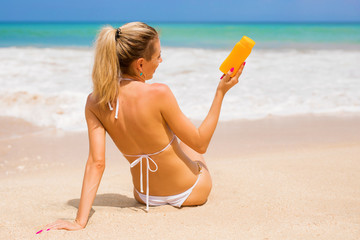 Woman holding sunscreen bottle on the beach