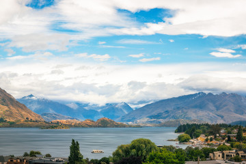 View of Wanaka lake and alpine resort town with the mountain range in the background in New Zealand, on a cloudy summer day.