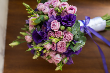 Wedding bouquet with purple and pink roses, violet flowers lying on a wooden windowsill
