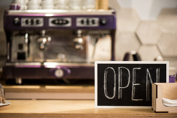 selective focus of open blackboard on wooden counter in cafe