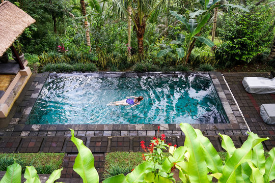A young girl is floating in the infinity pool in the jungle. Taken on the island of Bali in Ubud.