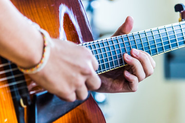 Close-up view of guitar and musician's hands