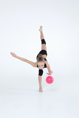 Rhythmic gymnastics caucasian blonde girl in black suite performing athelete exercises with pink ball handling abilities showing flexibility and acrobat balance on white background isolated