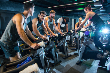 Group of happy sporty people riding spinning bikes together in gym.