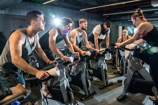 Group of sporty people having spinning class at gym.