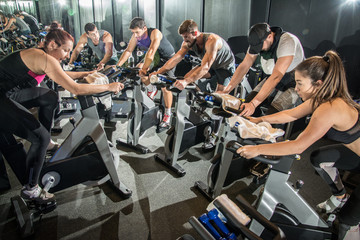 Group of fit people working out on spinning class in gym.