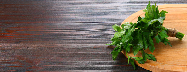 Fresh green parsley on the wooden table, selective focus. Banner