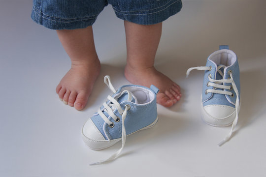 the first baby shoes on the background of the  babies feet